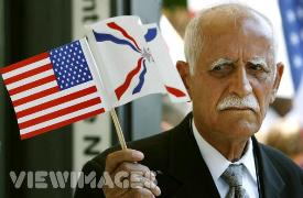 Assyrian flag held high by an elderly Assyrian man in USA